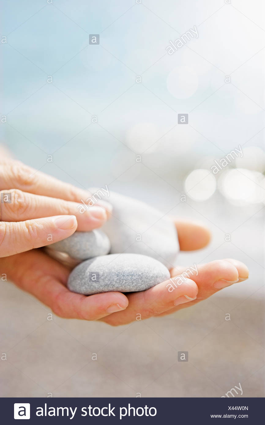 Estonia, Female hands holding white pebbles - Stock Image