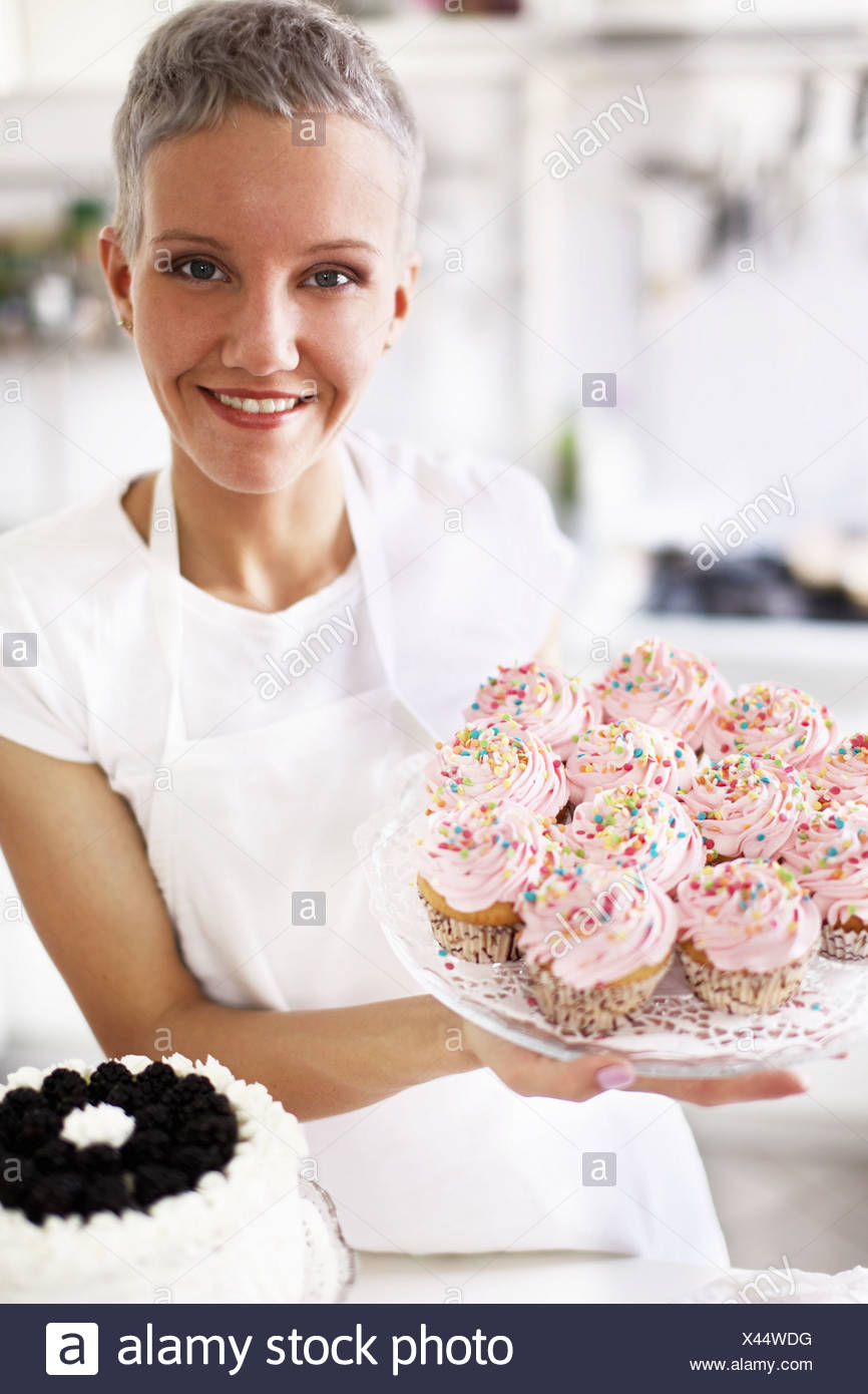 Portrait of woman holding hand made cupcakes - Stock Image