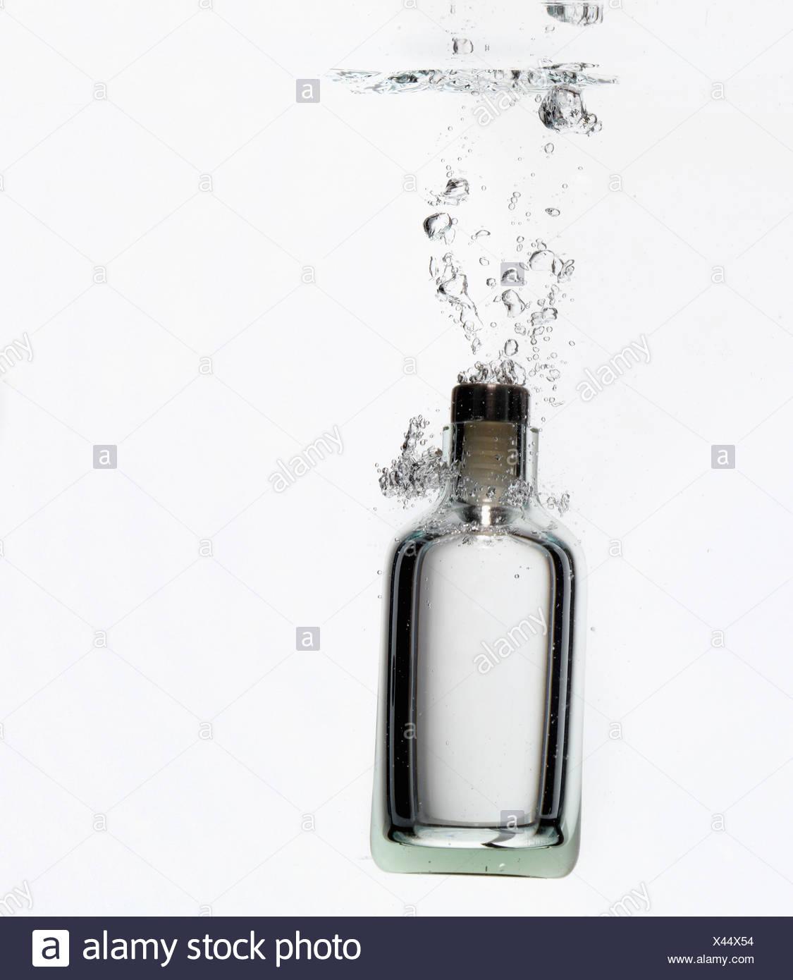 Bottle splashing in water - Stock Image