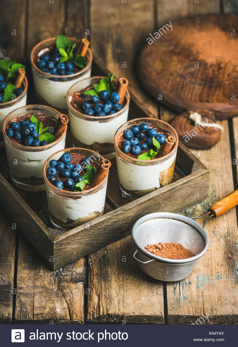 Homemade Tiramisu dessert in glasses with cinnamon, mint and fresh blueberries in wooden tray and sieve with cocoa powder over r - Stock Image