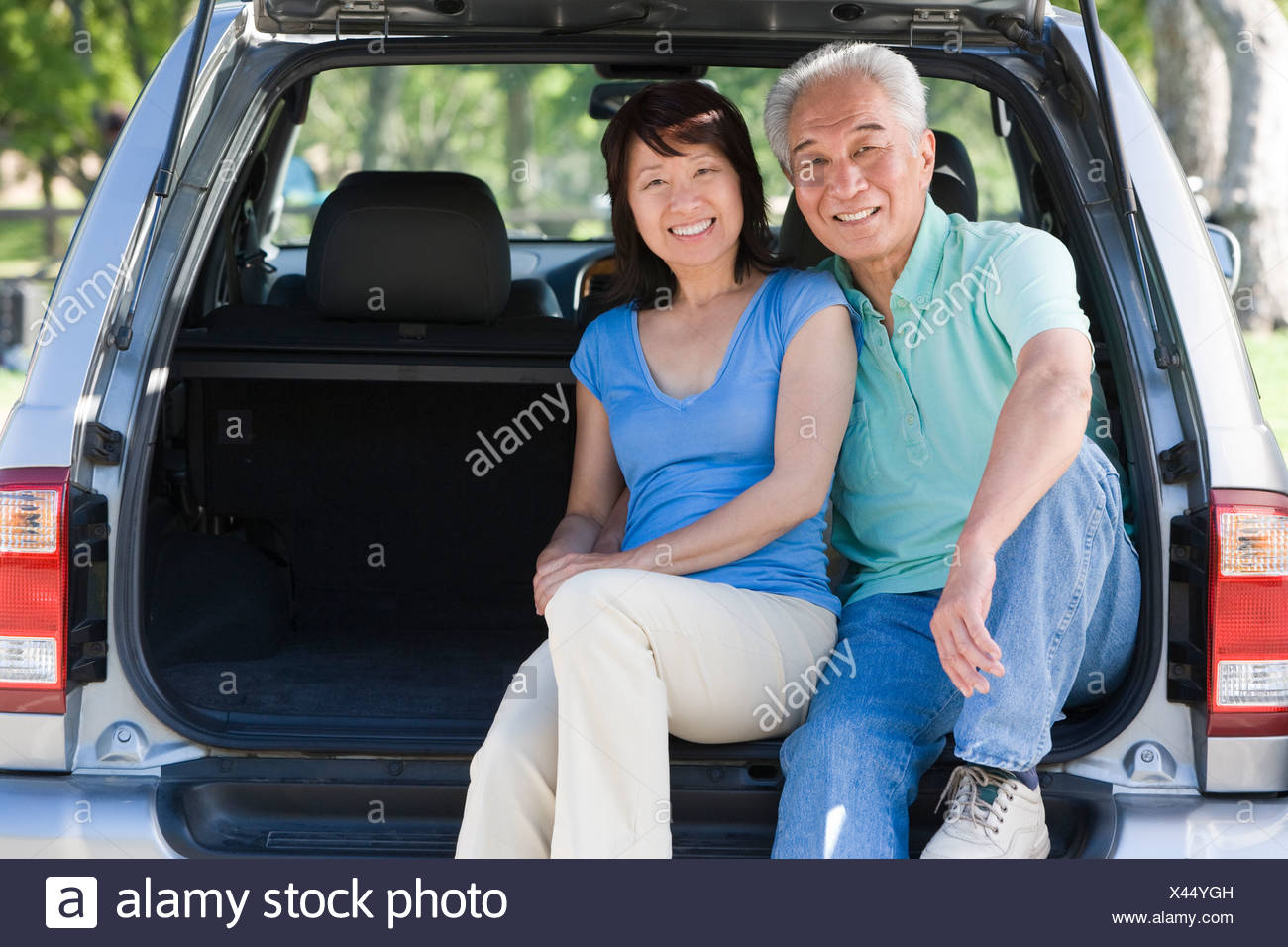 Couple sitting in back of van smiling - Stock Image