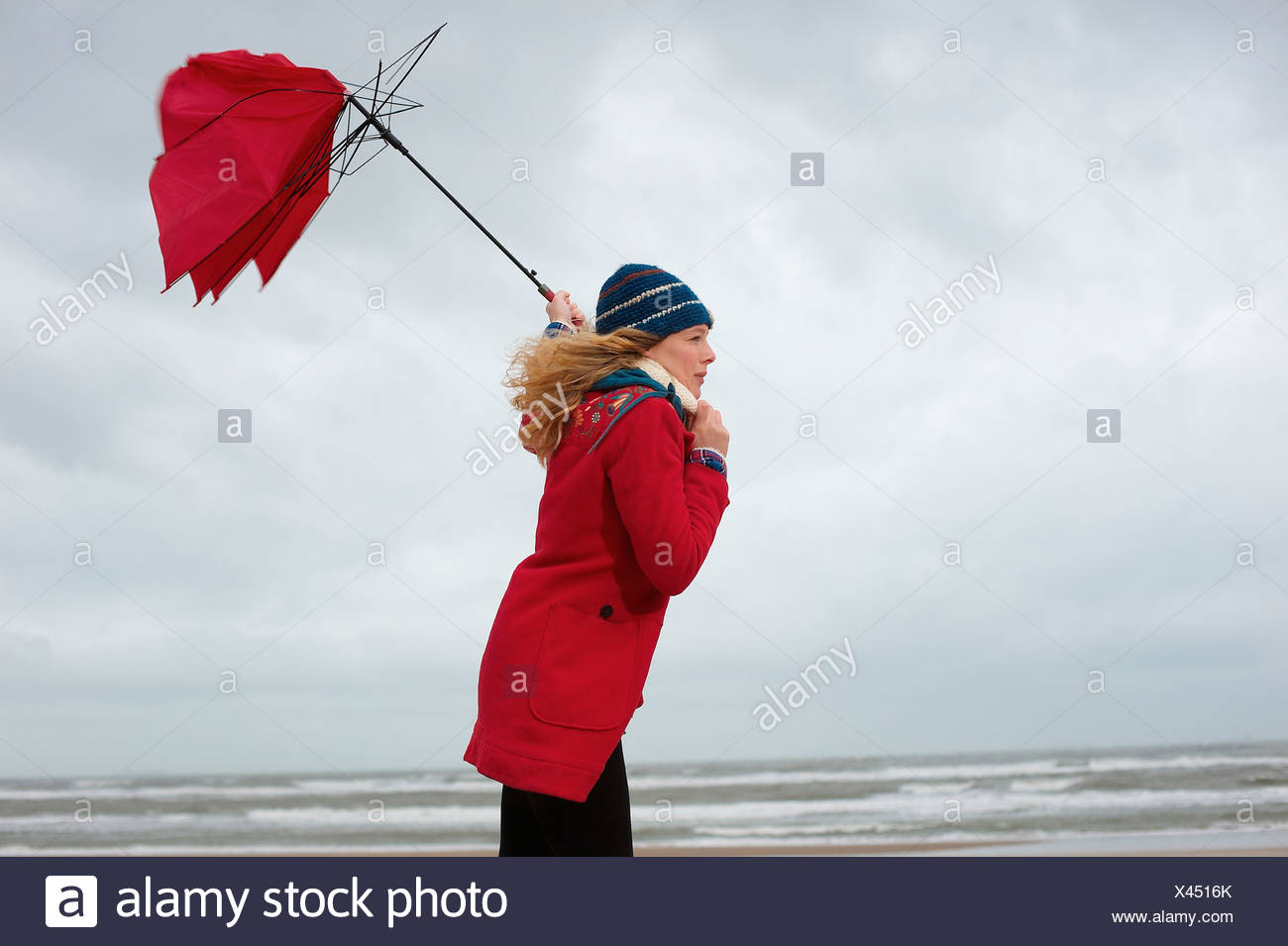 A woman standing on a beach with her umbrella blowing inside out - Stock Image