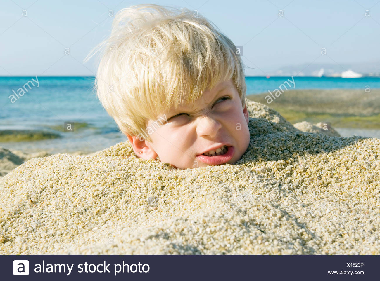 Young boy buried in the sand scowling. - Stock Image