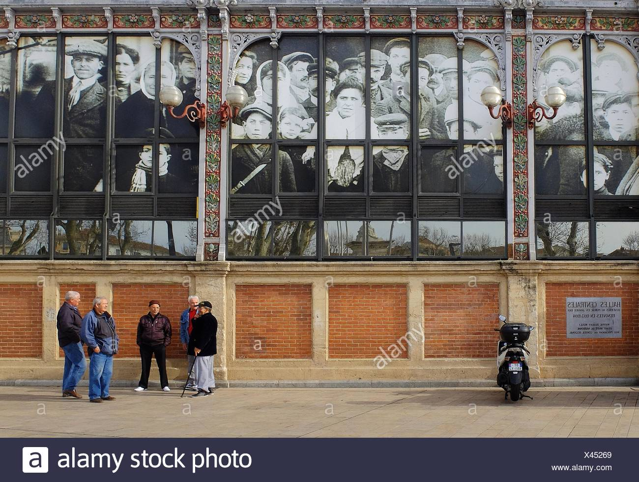 The windows of the ''Halles de Narbonne'' are decorated with photographic images of the people of 1900s Narbonne, France who built and shopped in - Stock Image