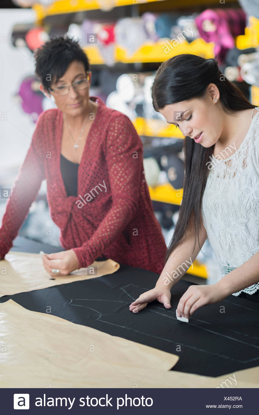 Two seamstresses chalking outline onto textile on work table - Stock Image