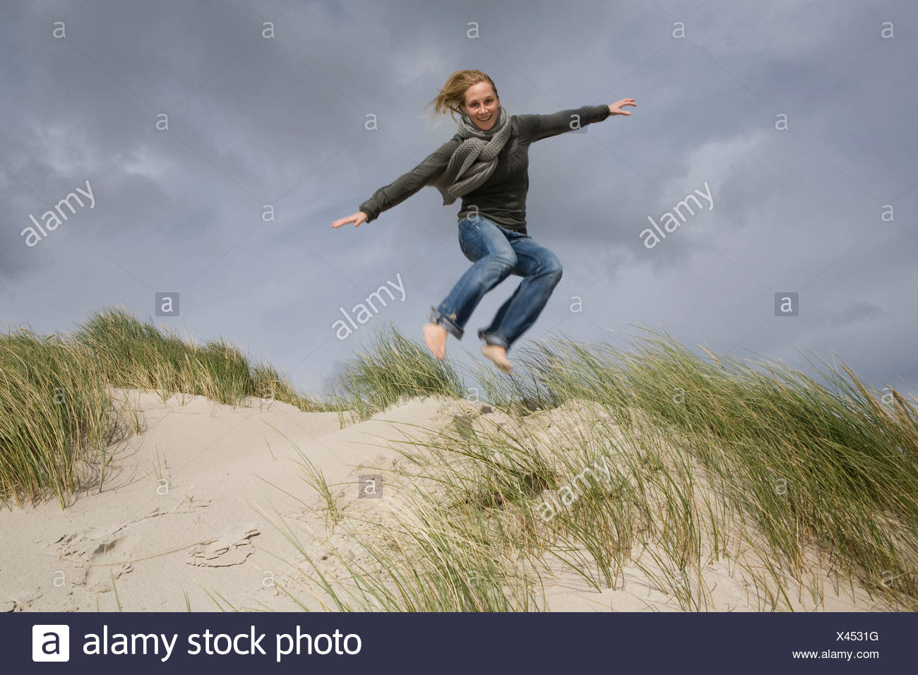 Germany, Schleswig Holstein, Woman in sand dunes, jumping - Stock Image