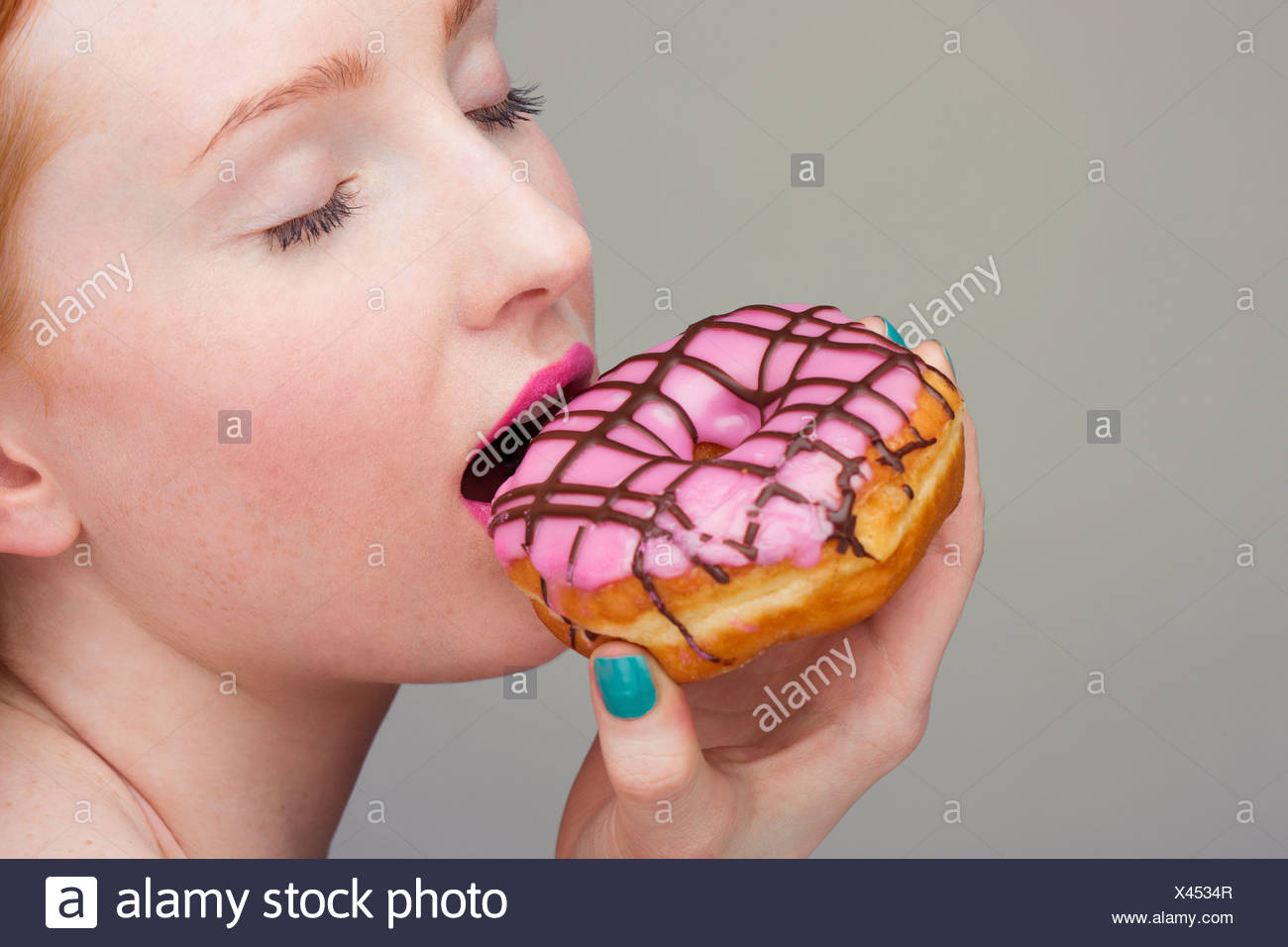 Young woman biting donut - Stock Image