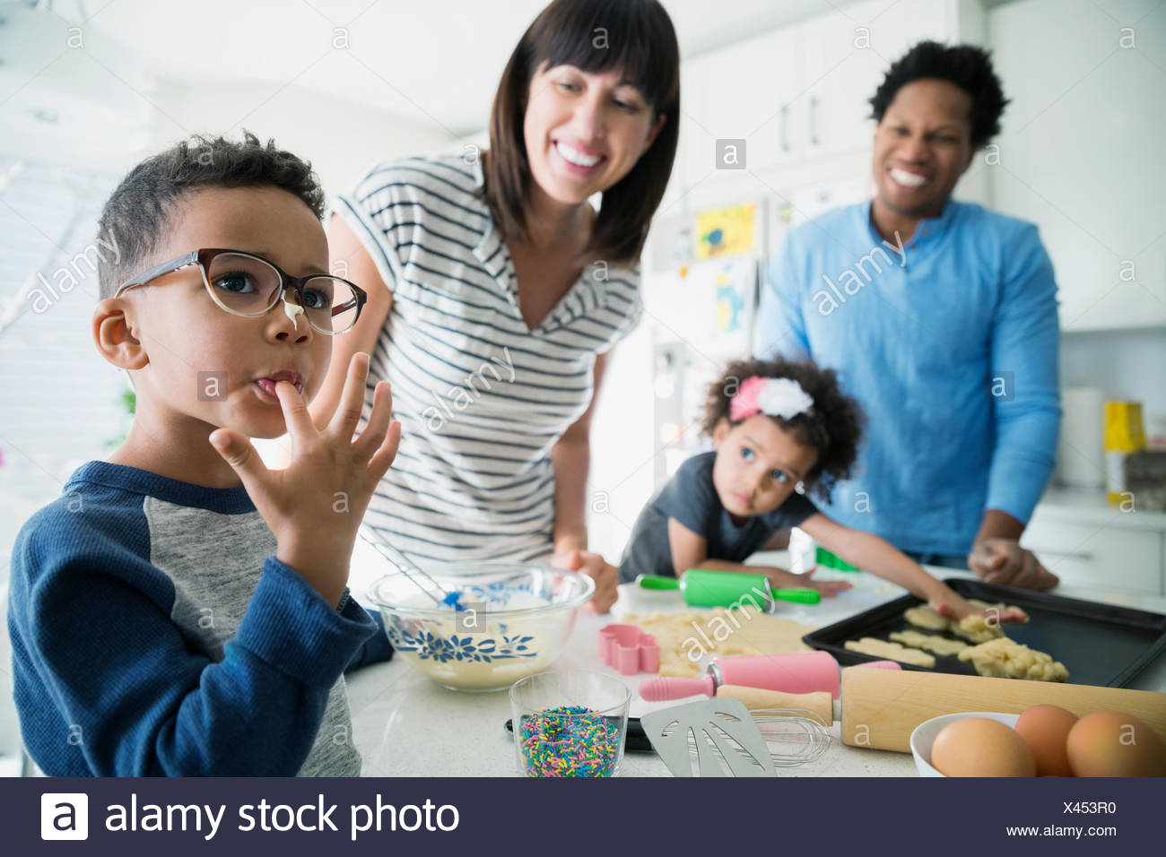 Boy with cookie dough on nose licking finger - Stock Image