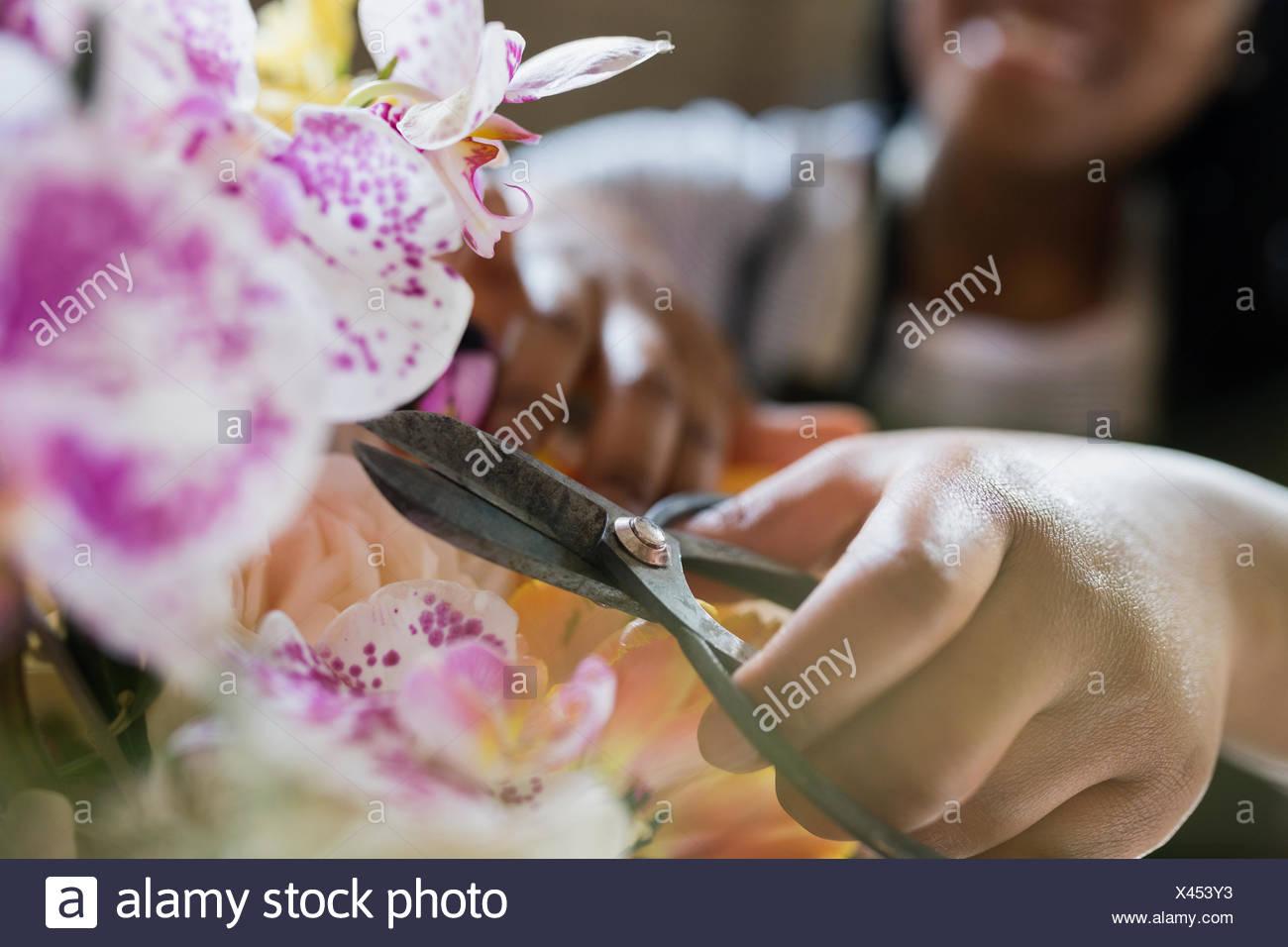 Close up florist with scissors arranging bouquet - Stock Image