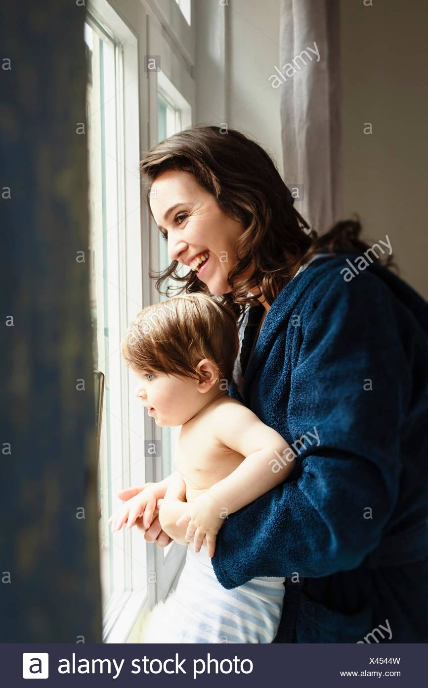 Mother and baby son looking through window - Stock Image