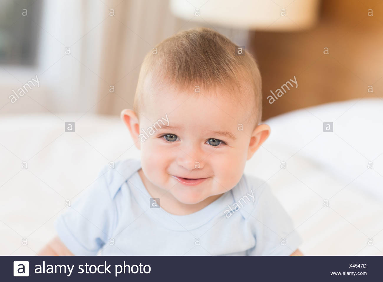 Baby boy in blue babygro - Stock Image