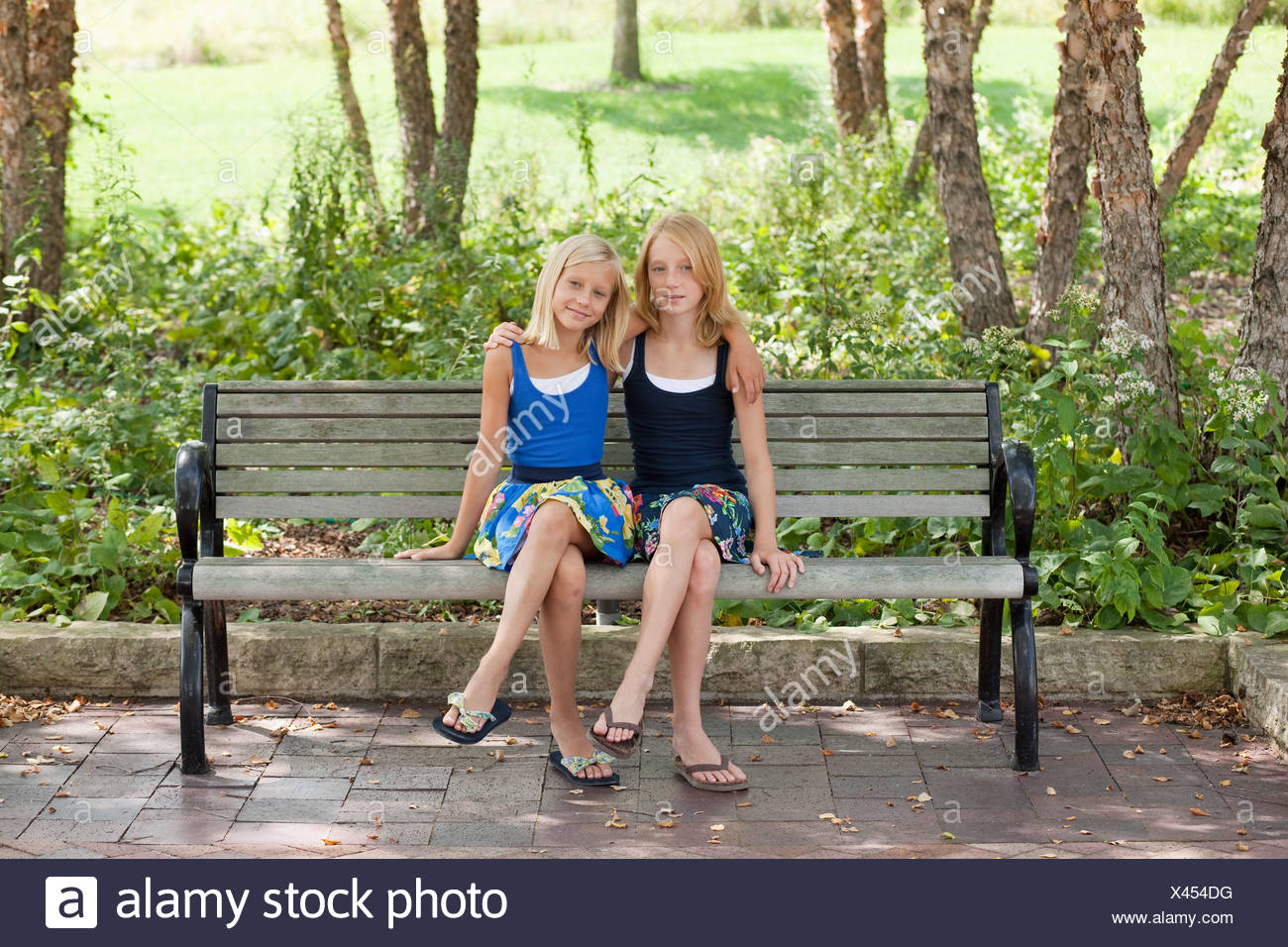 Two Girls legs crossed on a bench - Stock Image
