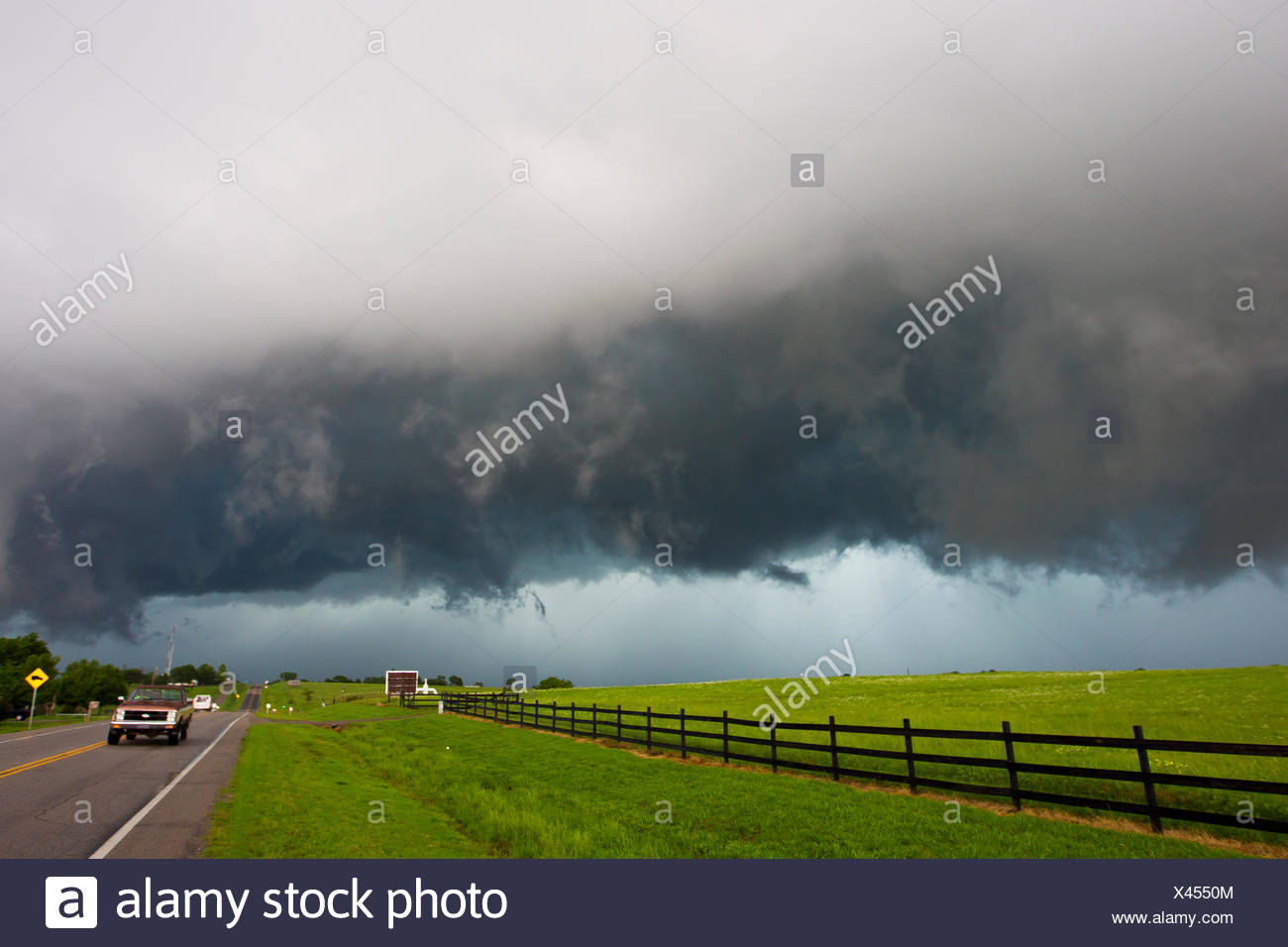 Dark skies and dangerous driving conditions from a supercell thunderstorm. - Stock Image