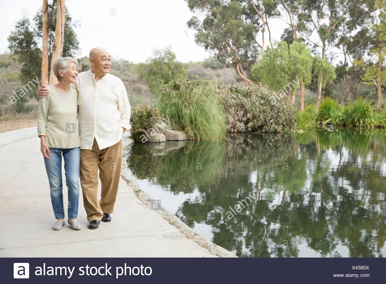 Senior couple walking beside lake - Stock Image