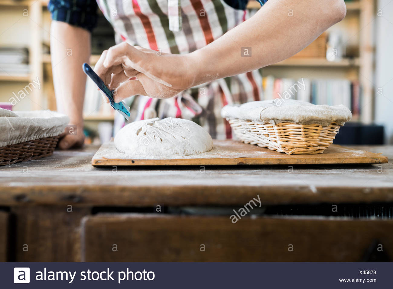 Midsection of baker making design on dough at table in bakery - Stock Image