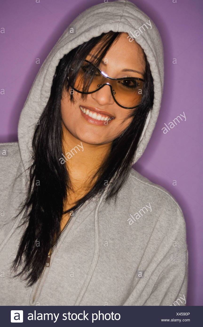 Studio portrait of young woman in sunglasses and hooded top - Stock Image