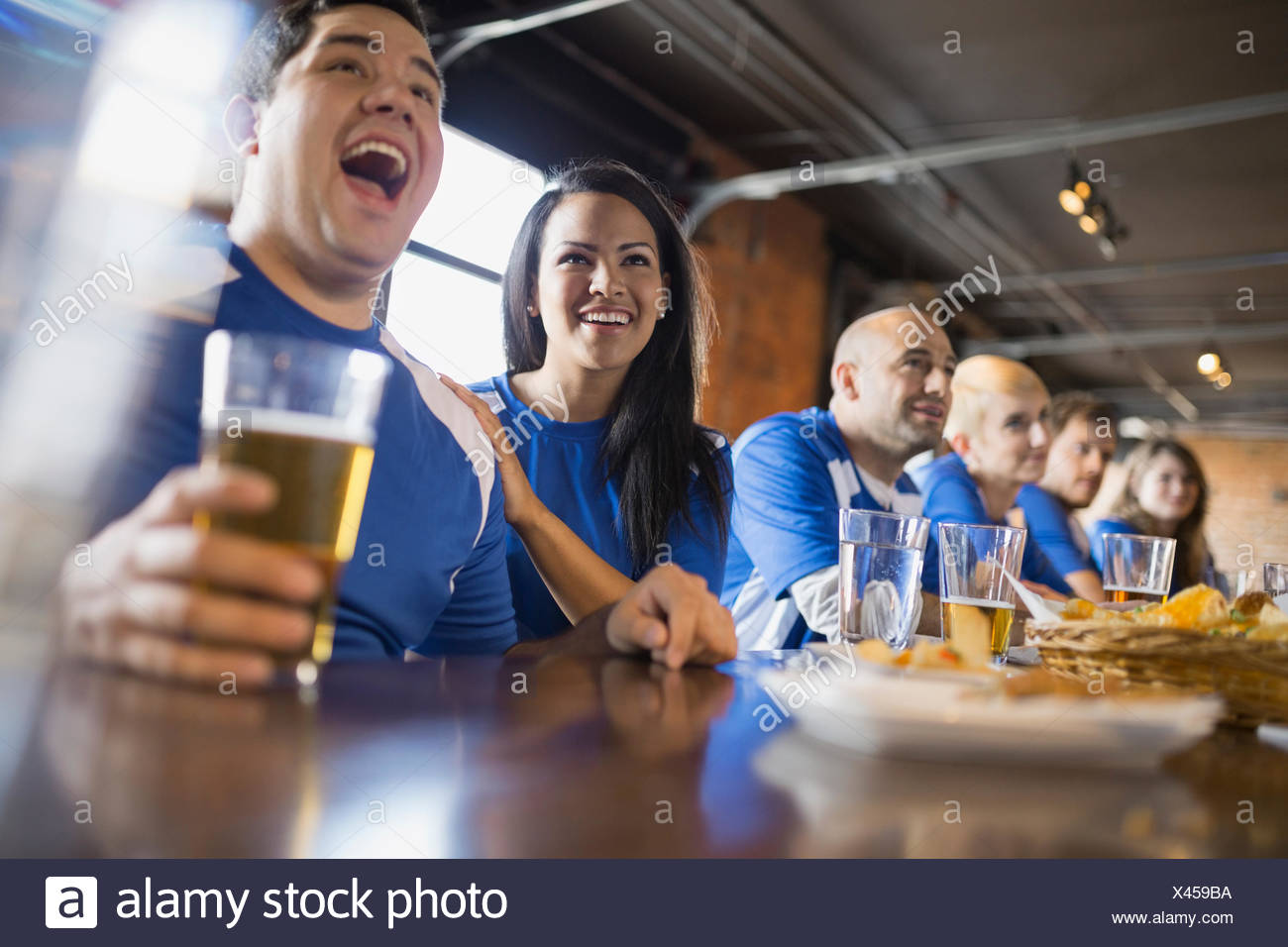 Sports fans watching TV at bar in pub - Stock Image