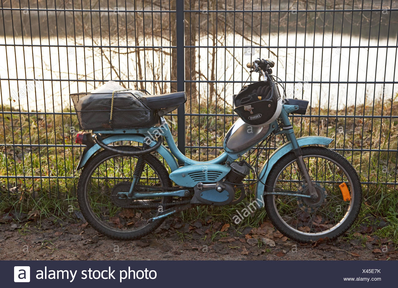 Motorbike, fence, leant, - Stock Image