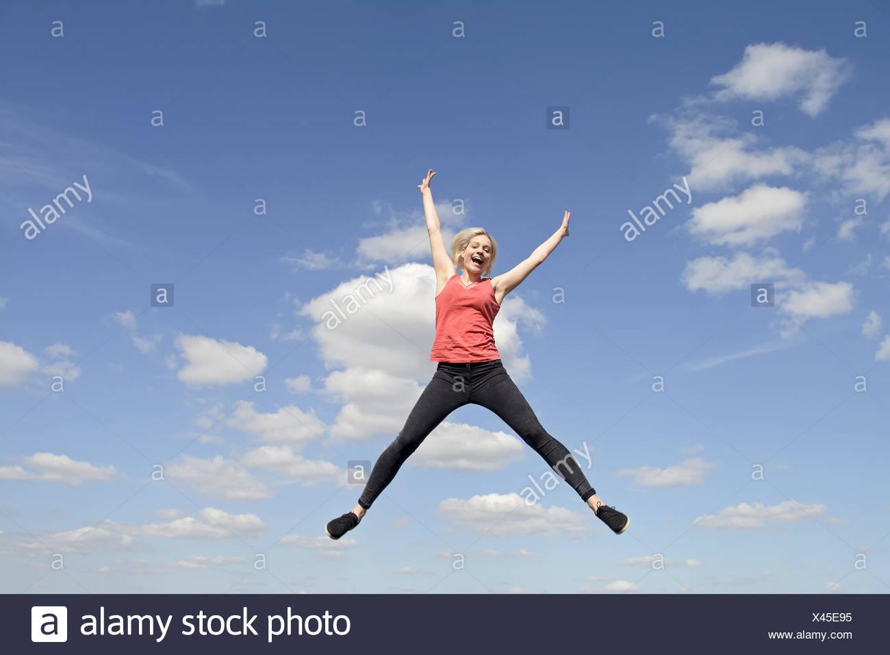 joyful young blond woman leaping - Stock Image
