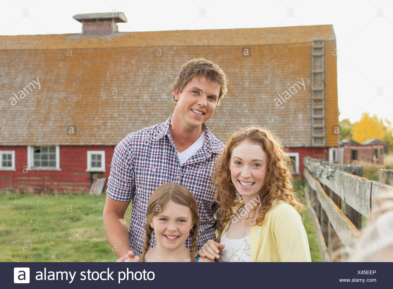 Portrait of young family in front of barn. - Stock Image