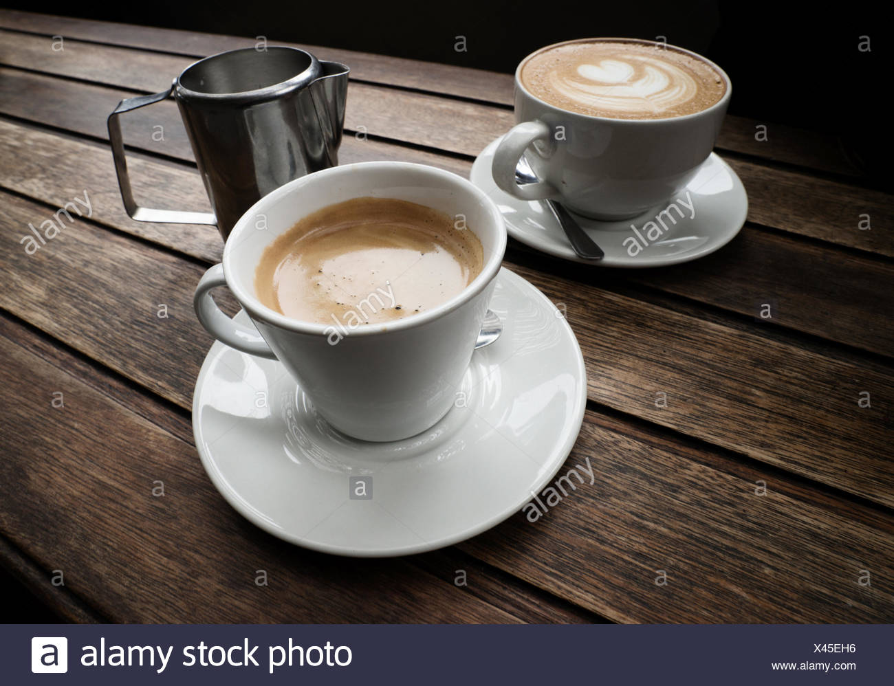 Two cups of coffee on wooden table - Stock Image