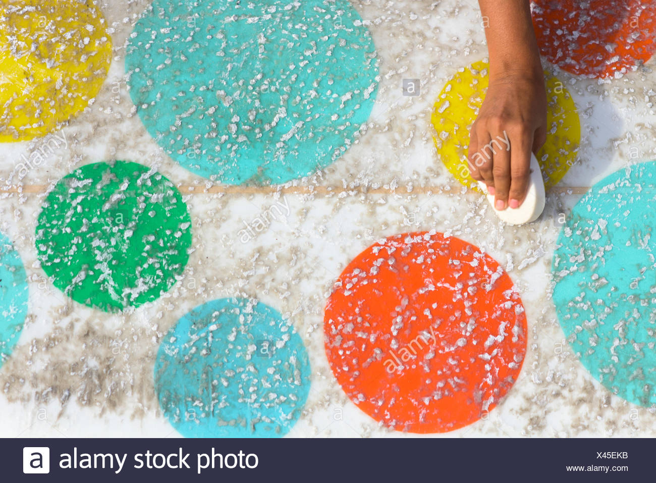 Vanessa Yeager waxes her colorful longboard surfboard in Newport Beach, Calif. - Stock Image