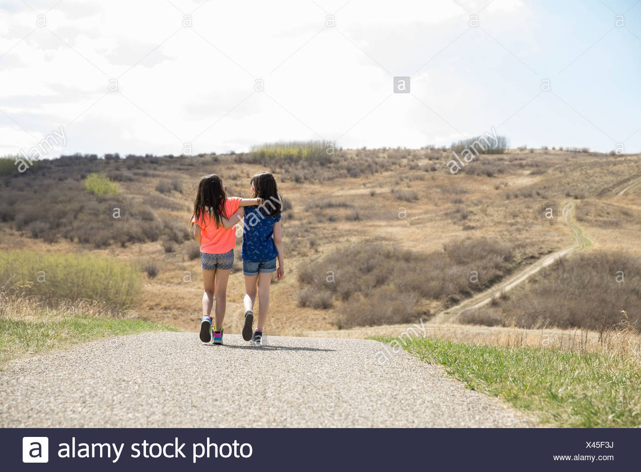 Friends with arms around each other walking down a pathway - Stock Image