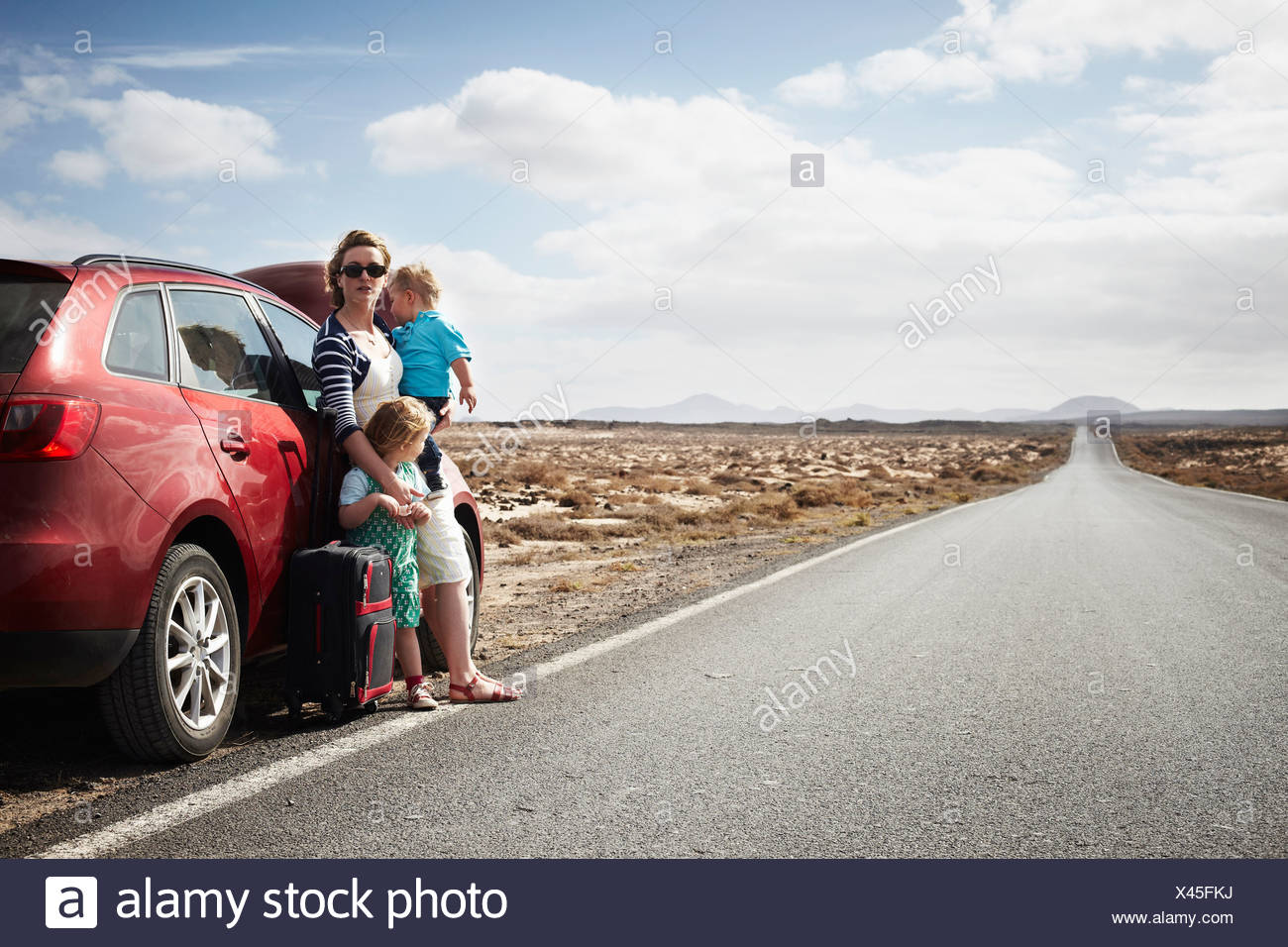 Family standing by broken down car - Stock Image