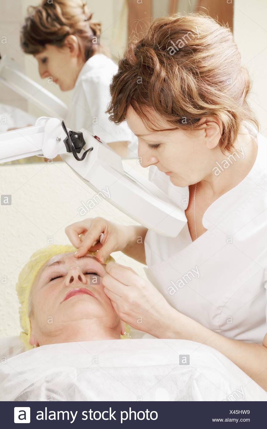 Beautician does eyebrows tweezing procedure - Stock Image