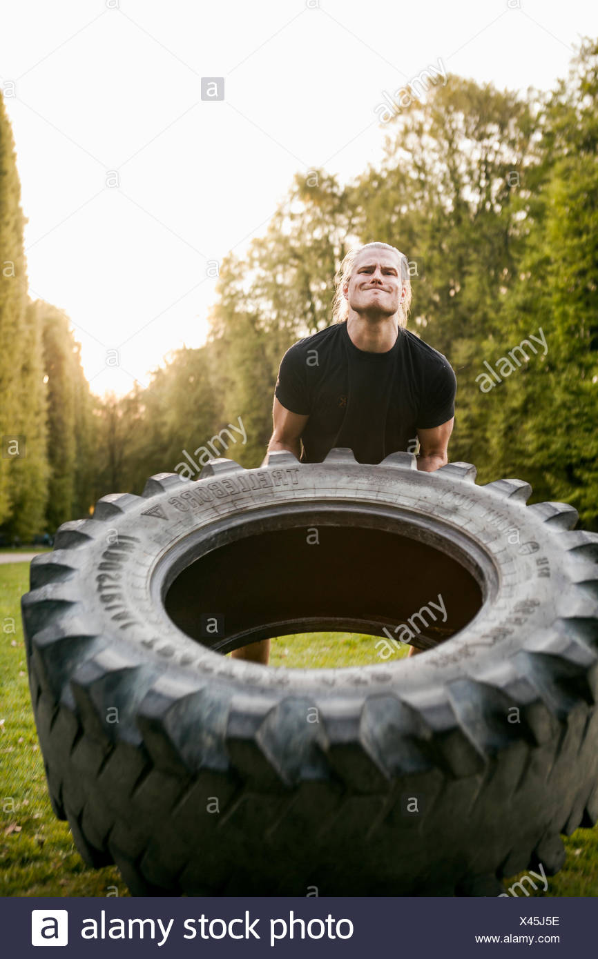 Young man lifting large tire in park - Stock Image