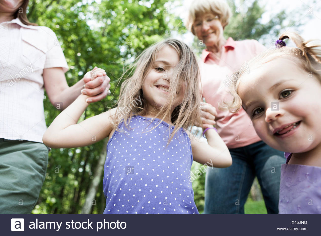 Three genration family holding hands, candid - Stock Image