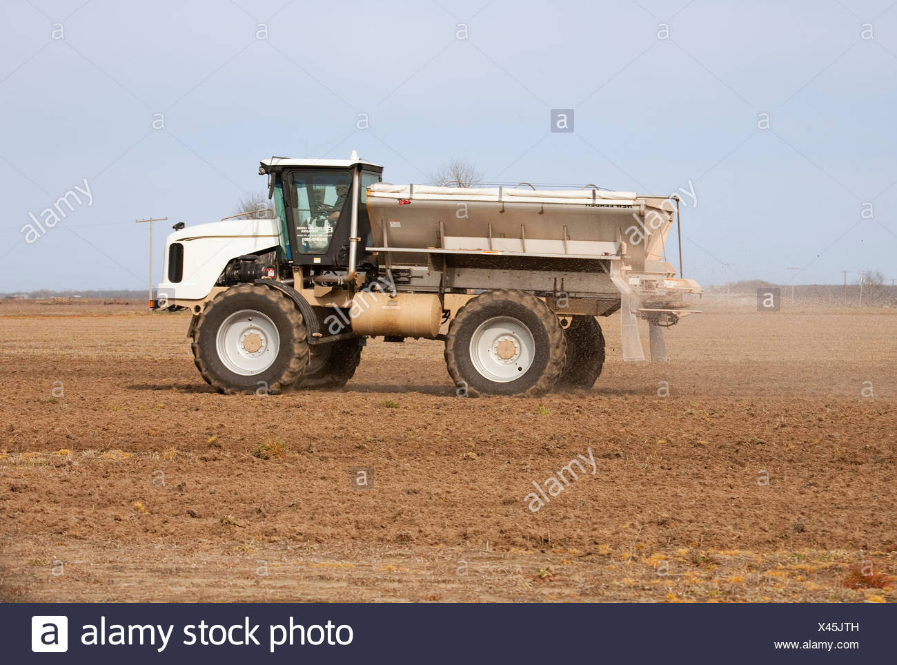 Agriculture - A New Leader spreader applies dry fertilizer to a bedded field in late Winter / Eastern Arkansas, USA. - Stock Image