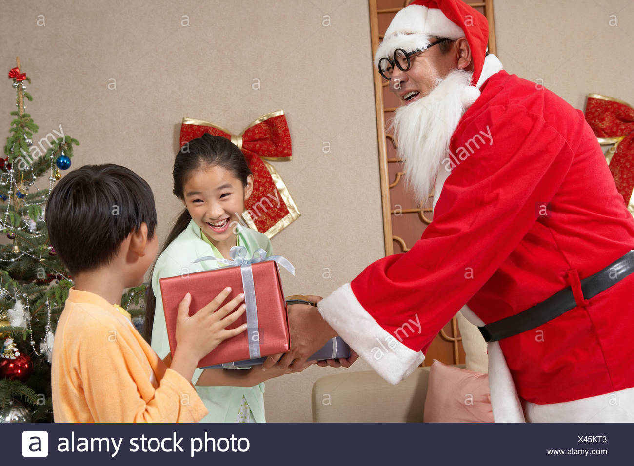 Santa Giving Presents To Young Excited Children - Stock Image