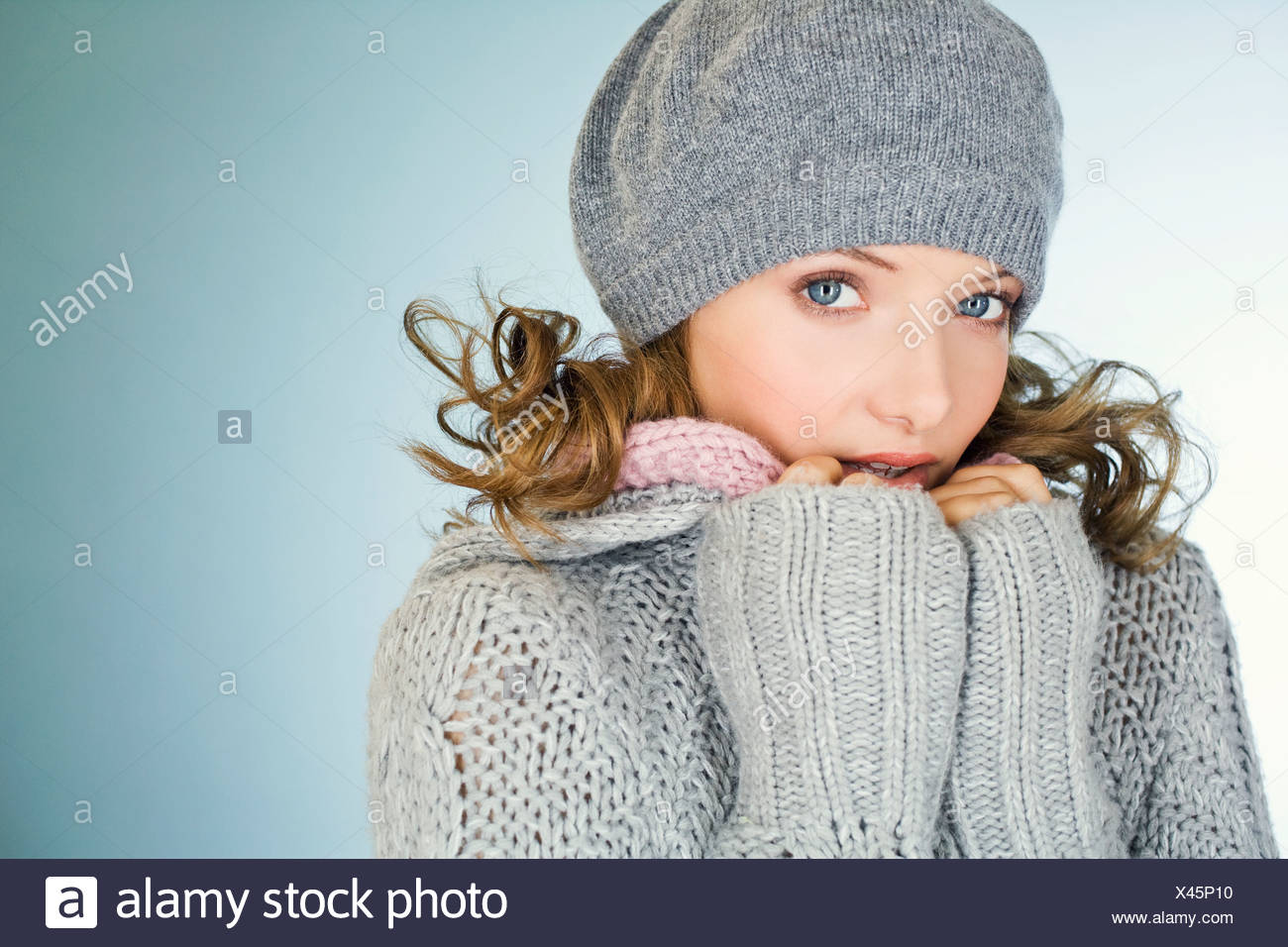 A young woman wearing a grey woollen hat, trying to keep warm - Stock Image