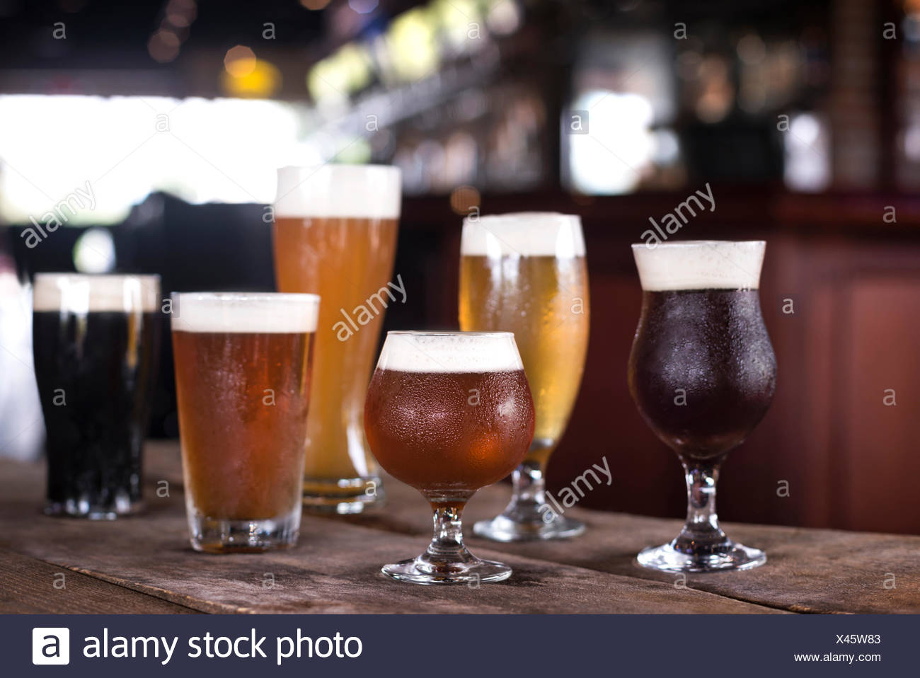 A variety of beers in a variety of glasses on a rustic wood surface with bar in background. - Stock Image