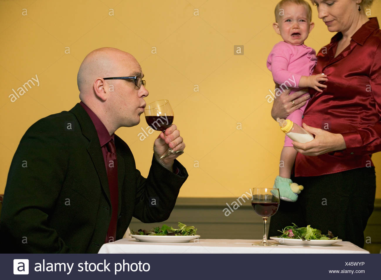 Mother holding crying baby as husband sips wine - Stock Image