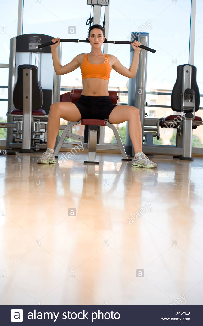 Woman using exercise equipment in gym, low angle view - Stock Image
