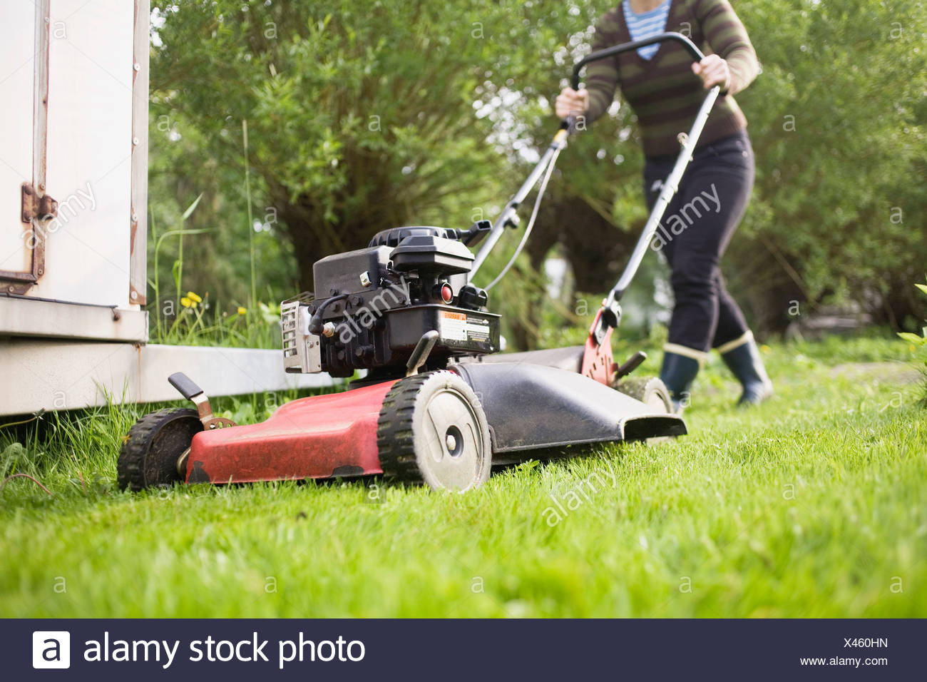 Women pulls a lawnmower - Stock Image