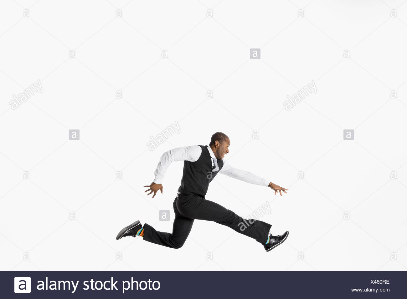 Exuberant businessman running and jumping against white background - Stock Image