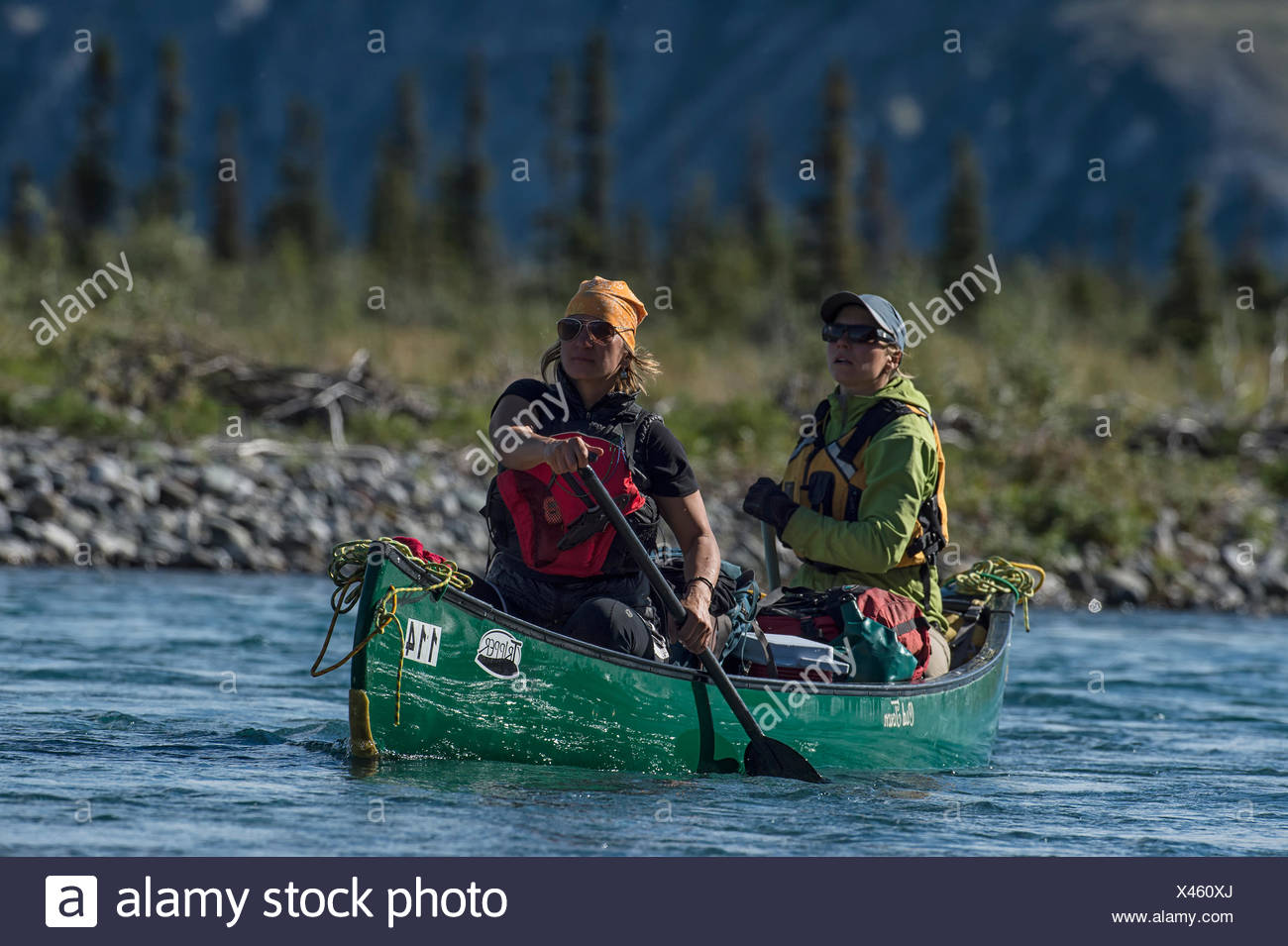 Two women canoe the crystal clear waters of the Wind River. The River, a tributary of the Greater Peel Watershed, has some of the cleanest and clearest water on our planet. - Stock Image