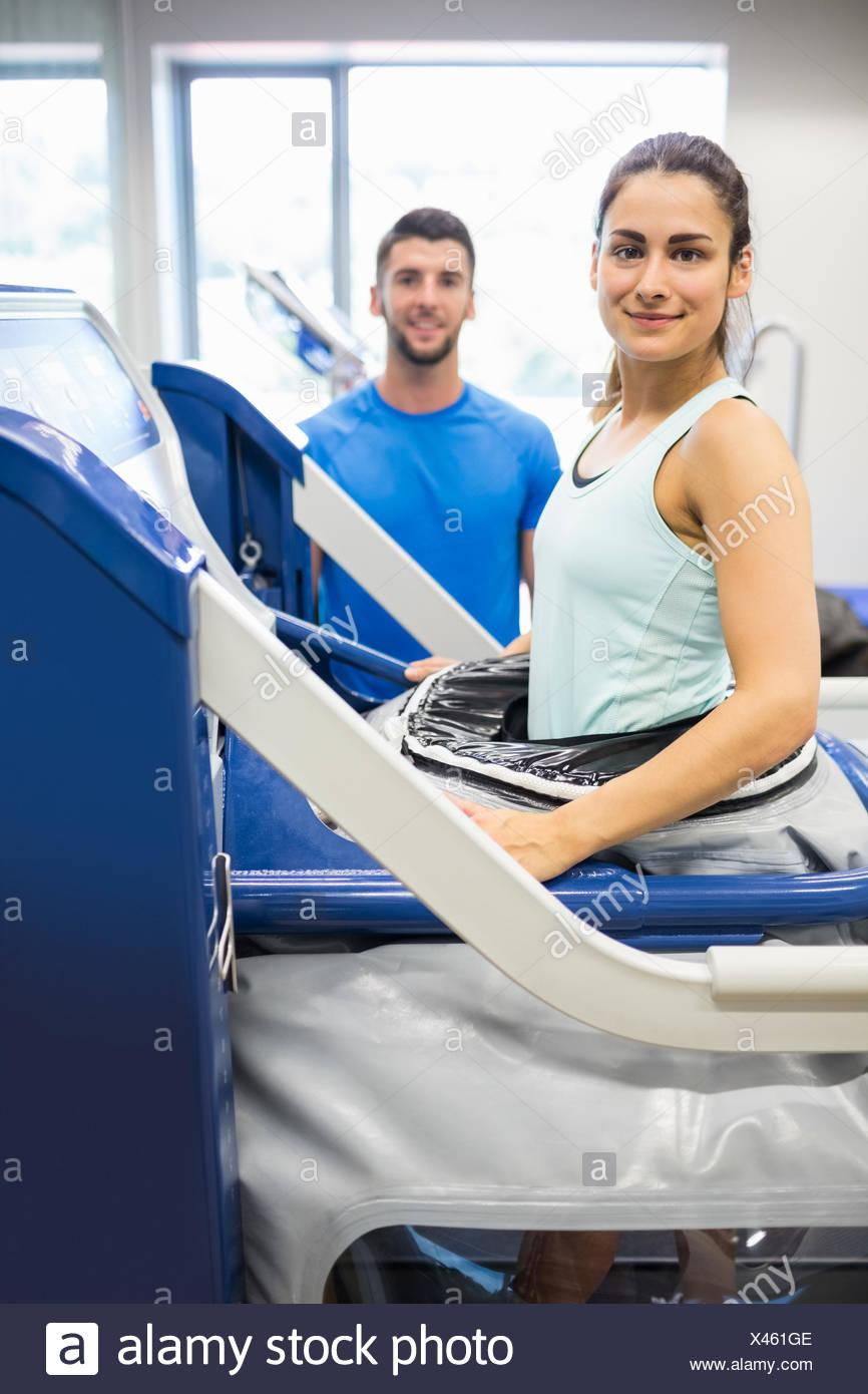 Woman using an anti gravity treadmill beside trainer - Stock Image