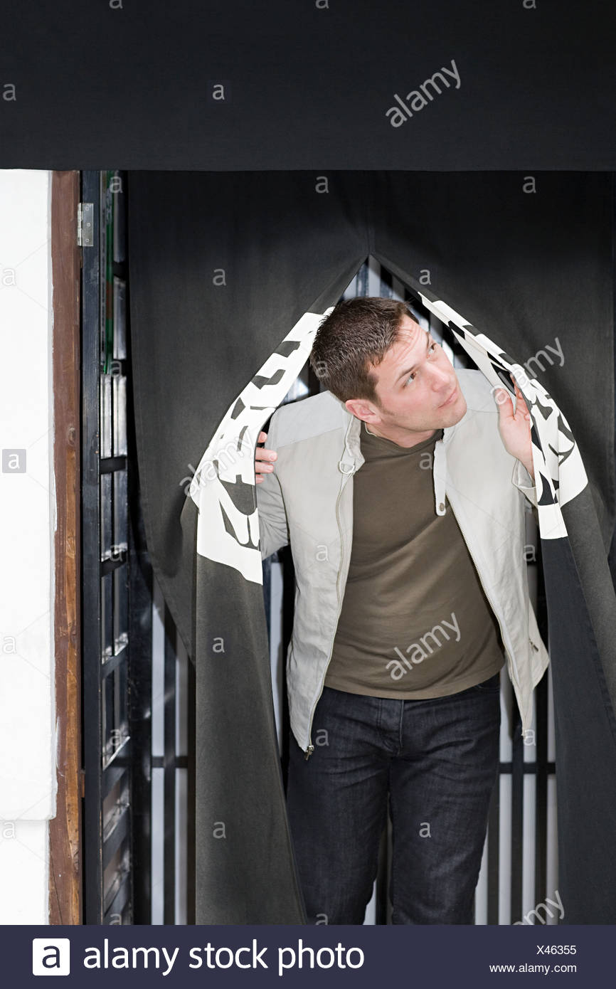 Man emerging from curtain - Stock Image