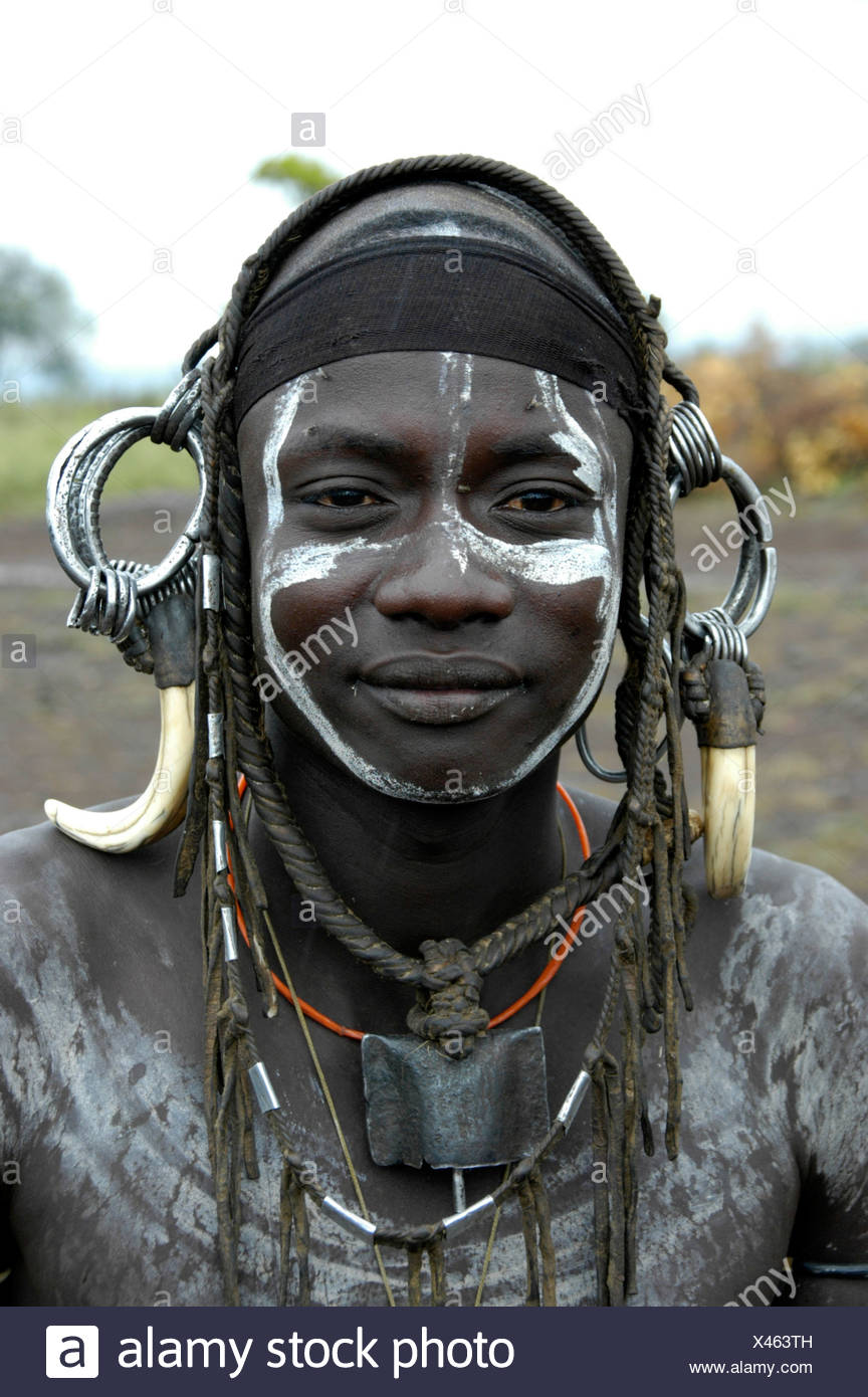 Portrait of a young man from the Mursi tribe, wild, heavy headdress made of teeth of a male boar, near Jinka, Ethiopia, Africa - Stock Image