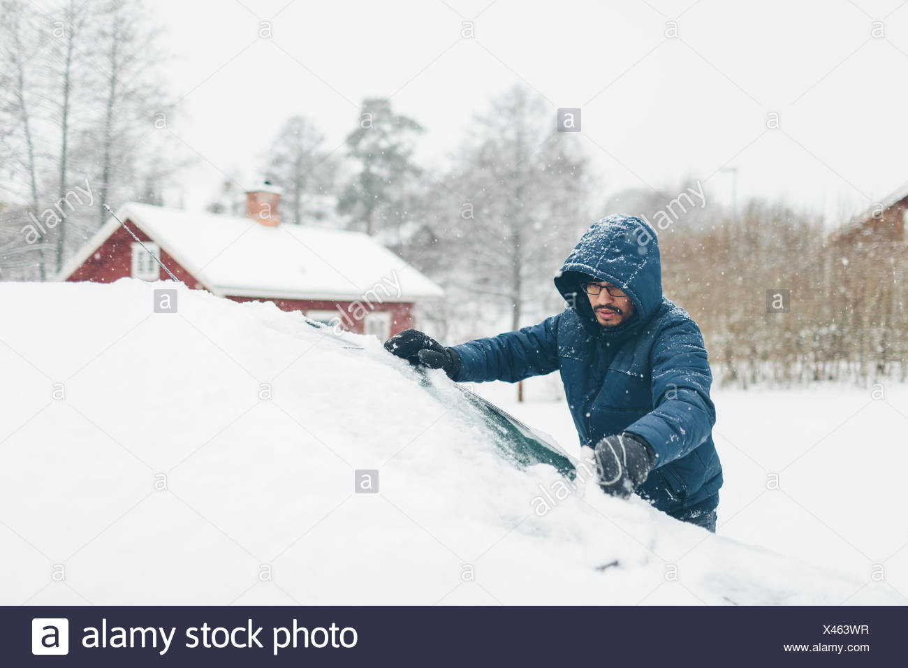 Man clearing snow from his car - Stock Image