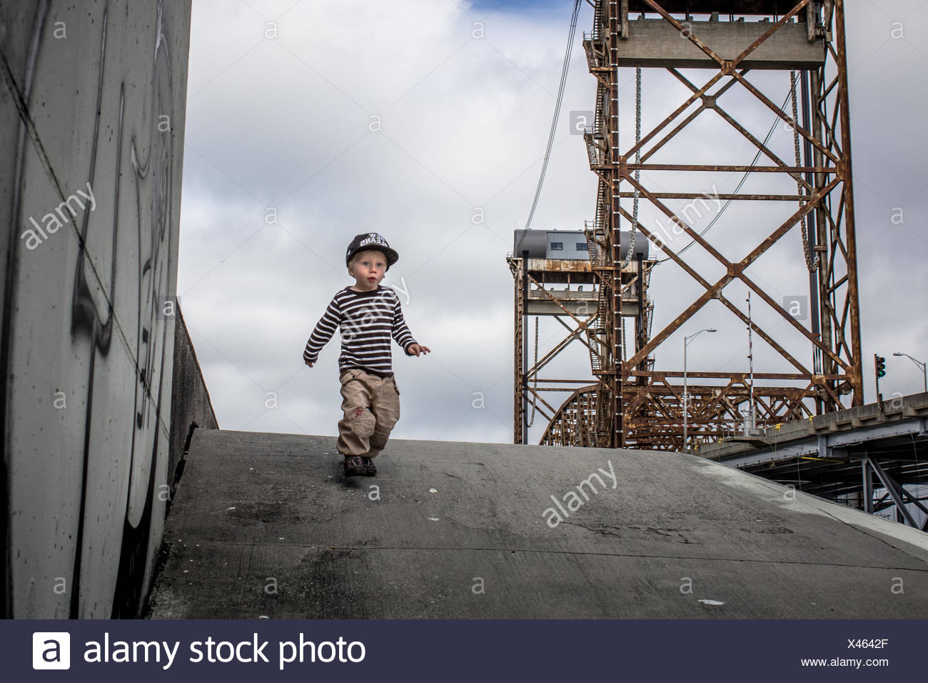 USA, Louisiana, New Orleans, Boy (2-3) running down from levee in Lower ninth ward, Claiborne Bridge in the background - Stock Image