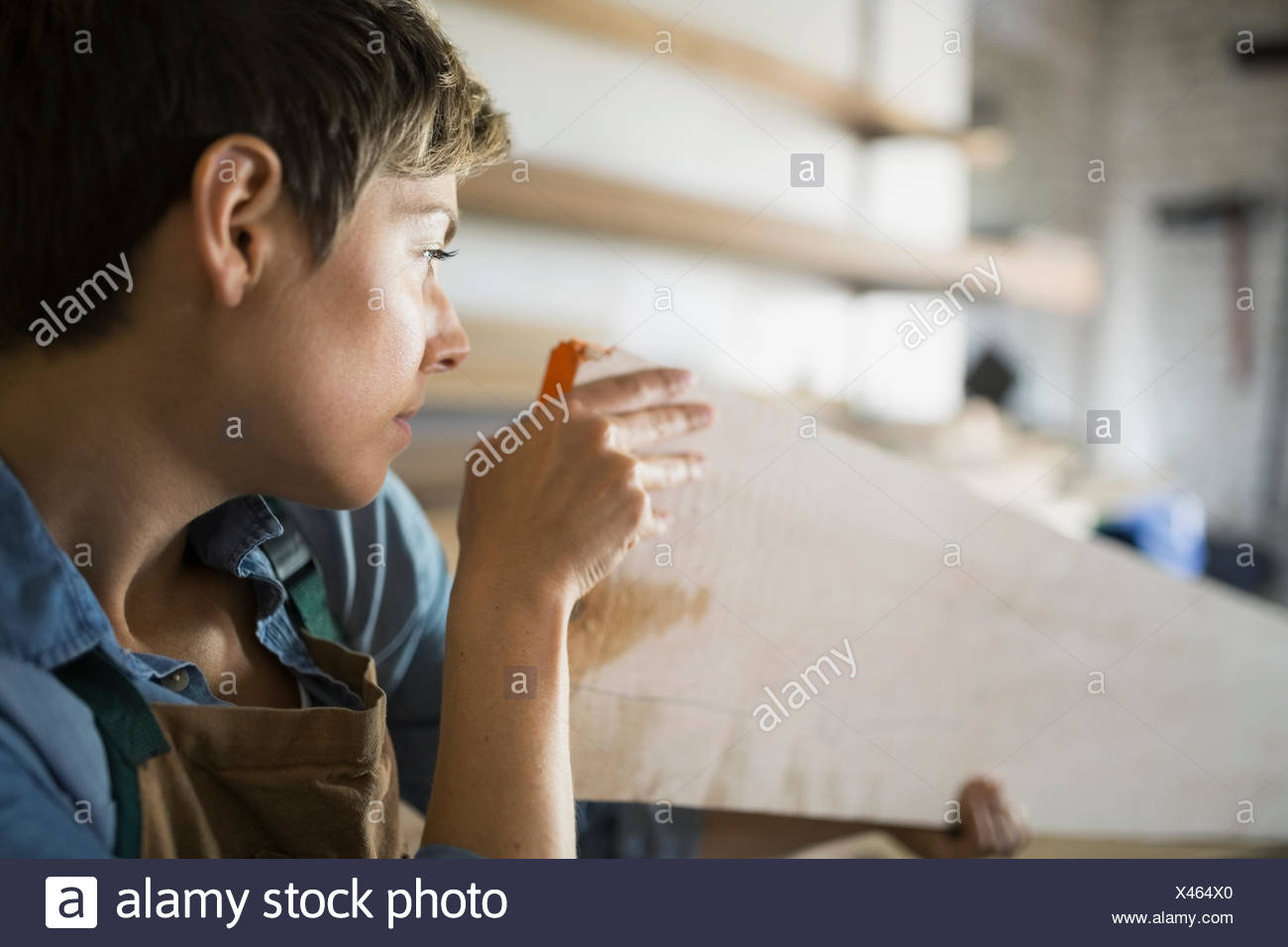 Woman examining wood plank in workshop - Stock Image