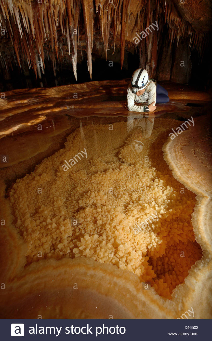 A female cave explorer looks into a very pretty Gour Pool. The floor of which is covered with 'dog tooth' crystals. The edges of - Stock Image