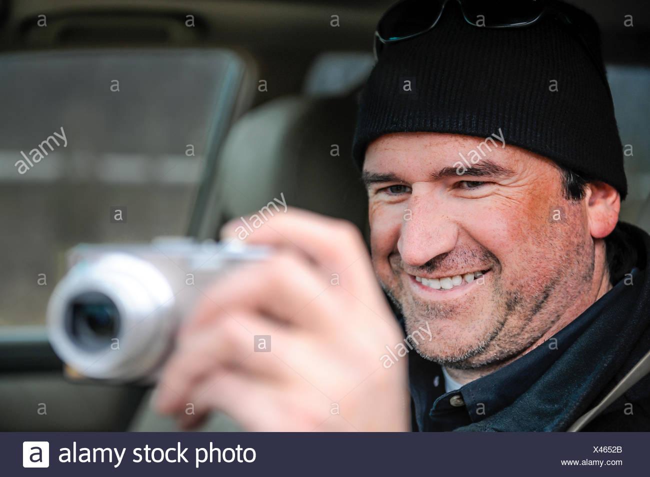 Smiling man taking photo through his car window - Stock Image