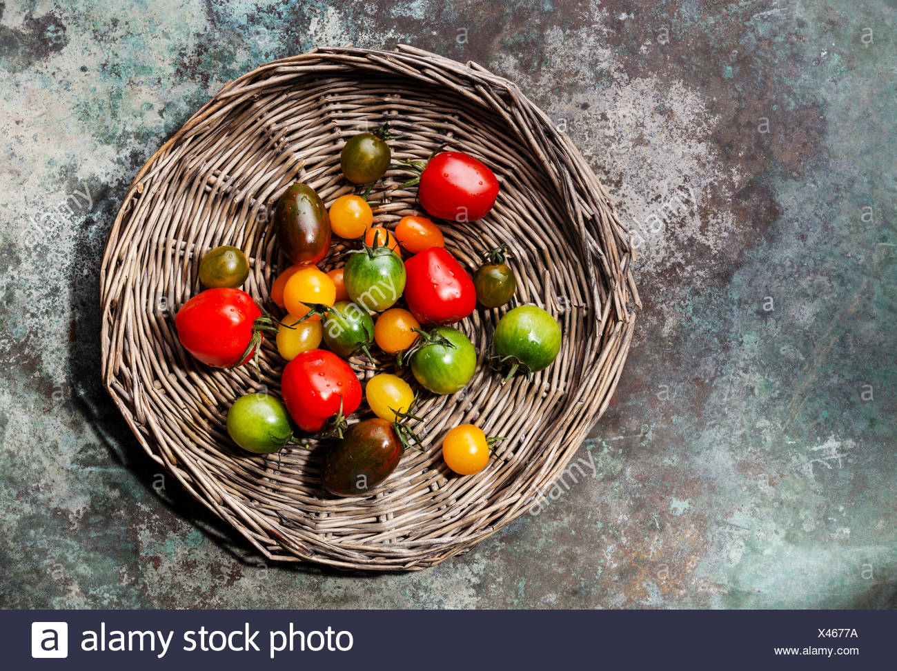 Ripe fresh colorful tomatoes on wicker tray on metal background - Stock Image