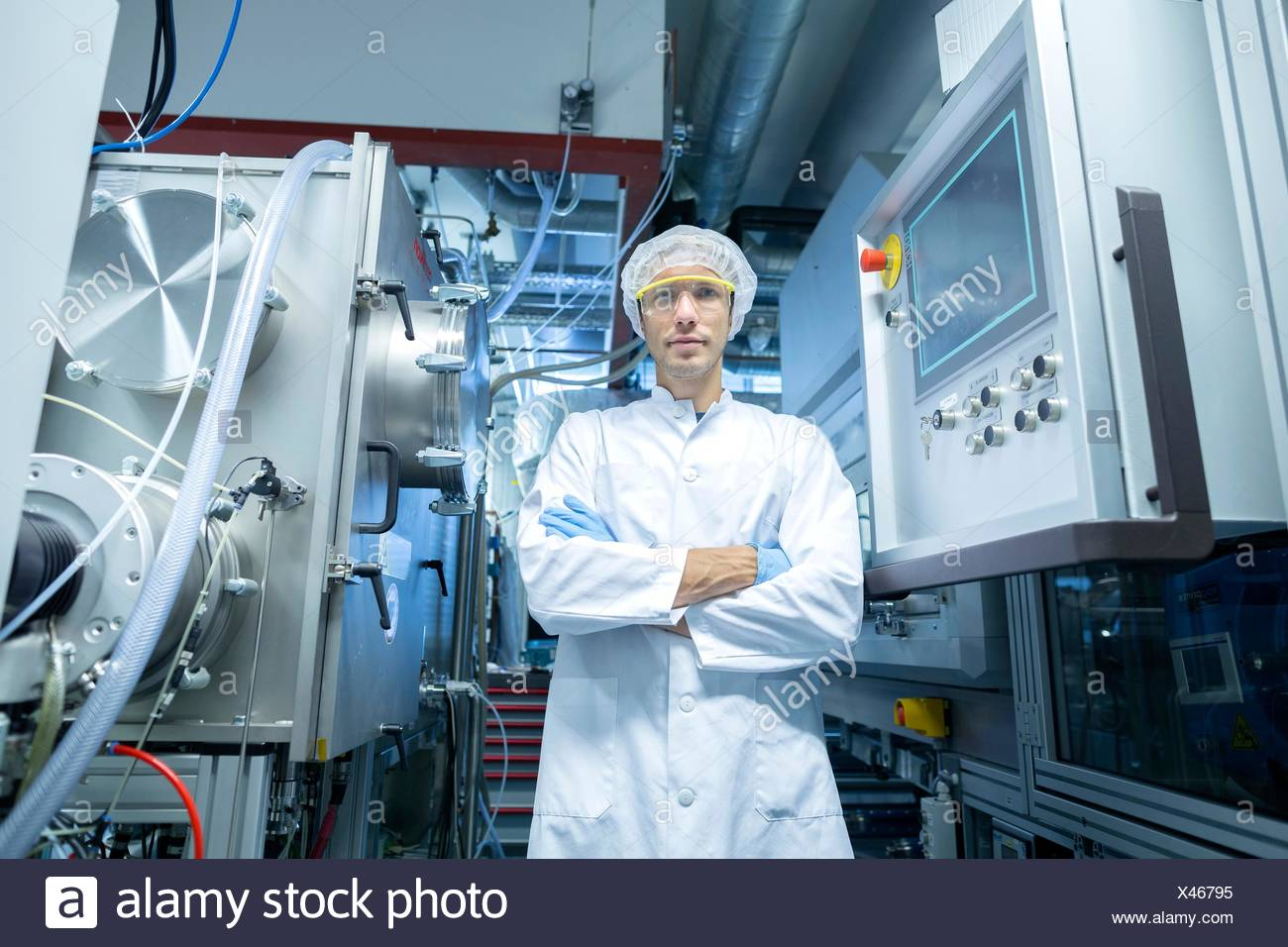 Portrait of male scientist with arms folded in lab cleanroom - Stock Image